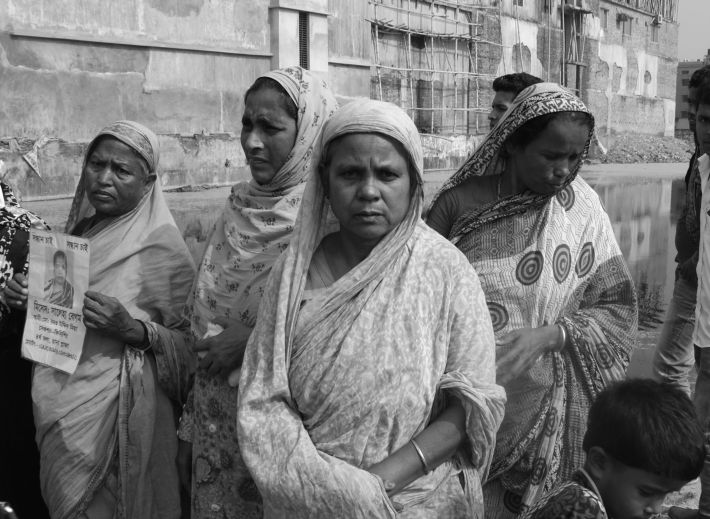 Mothers who lost their children waiting at the site of Rana Plaza